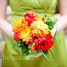 pretty orange dahlia bouquets accented with green grass loops.   it's listed as a bridesmaid bouquet but whatevs it'd be beautiful as a bride's