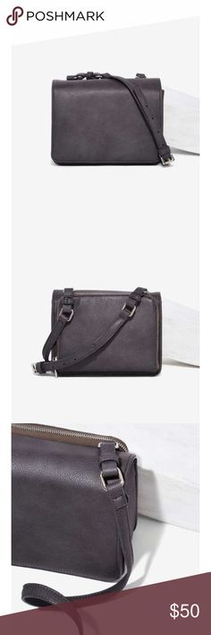 "Nasty Gal crossbody bag This crossbody is made in a slate gray vegan leather and features an adjustable shoulder strap, flap with snap closure, zip pocket with controlled opening at back, and one interior pocket. Fully lined.  *PU  *8.5""/21.6cm length  *6.75""/17.2cm height  *3""/7.7cm depth  *Imported Nasty Gal Bags Crossbody Bags"