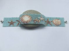 Sand Dollars and Starfish, super cute and bang on trend. This narrow Peyore Cuff has been beaded with Miyuki Delica beads, the Rolls Royce of Japanese Seed beads. The shells and starfish have been beaded in Creams, Bronzes and Golds, they are sitting on a gorgeous transparent