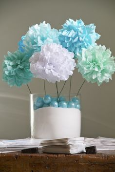 "Pom Pom centerpiece, I'd fill the vase with clear or colored stones, no sand or only colored sand. You can get a really ""full"" affect by having more pom poms at different heights. Cheaper than flowers but way more time consuming to make."