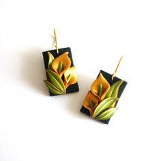 Aurum, golden Arum lilies on a black back drop and a bed of green leaves, made into a pair of earrings. Completely handcrafted using polymer clay!