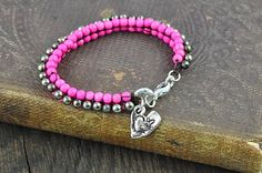 Vibrant Love Bracelet  This one of a kind vibrantly beaded bracelet is accented with a rustic silver double heart charm. A perfect bracelet to stack with other bracelets or to wear on its own as a statement piece.  #bracelets #pinkjewelry #heartbracelet #heartjewelry  islandcowgirl.com