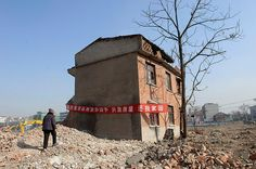 """Hefei, 2008: A nail house at a construction site being developed for apartment blocks. The banner reads """"strongly requesting the government to punish the developer who demolished my house, give back my home"""""""
