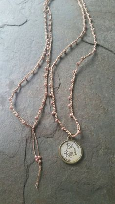 This necklace is a perfect for layering with your other favorite necklaces. The necklaces measures 38 . I crochet very small seed beads on nylon cord. A dainty charm hangs at the end. Lightweight and Versatile. Nylon cord: sable Seed beads: marbled opaque beige/pink Charm: bronze