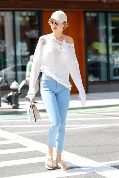Gigi Hadid in a white ripped sweater, light blue skinny jeans, and nude sandals while out to lunch in NYC.