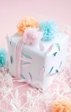 weiße Verpackungsideen mit kleinen Hasenohren und Pompons für ein kleines Kind
