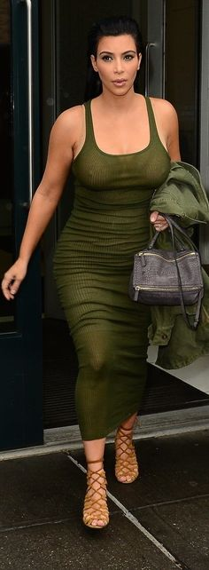 Kim Kardashian left her NYC apartment wearing an army green ribbed tank dress, which revealed a very thin neutral bra. She matched her slinky little number with a military-inspired jacket, gray crocodile satchel, and strappy caged sandals.