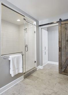 Love the alcove shower and sliding barn door in this master bathroom.