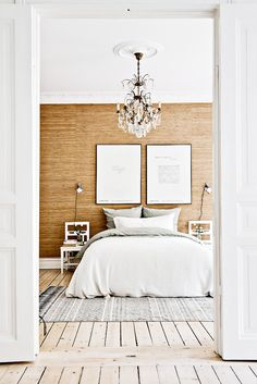 Gorgeous and luxurious bedroom with crystal chandelier, textured walls, neutral bedding and two oversized pieces of art above bed