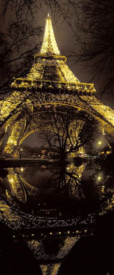 At the foot of Eiffel Tower at night, Paris, by photographer Arnaud Frich