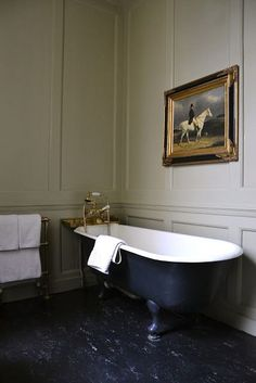 Victorian bathroom interior in country house with panelled walls, antique cast iron bath, towel rail and linoleum floor