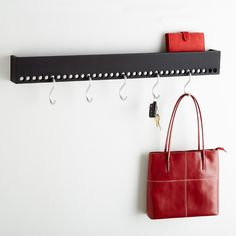 """Get ready to be hooked on our """"So-Hooked"""" Hook Rack. The modern design gives you the freedom to place your hooks where you want. It holds up to 33 pounds and is ideal for keeping everything from jackets and handbags organized in the mudroom to pots and pans in the kitchen. The flat space on top is handy for stashing your mobile phone or other small items. Additional hooks available."""