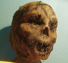 creator used styrofoam head, built up features with celluclay, carved out eye sockets. Sprayed head with spray mount, covered in burlap & used acrylic paints to shade & age it. Sealed with amber shellac & added gardening wire.