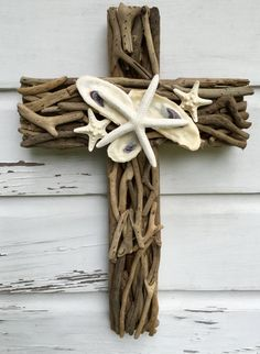 Driftwood Seashell Cross enhanced with a beautiful collection of shells including oyster shells and starfish. The driftwood cross measures 21 H x 13 W x 2 D and ships ready to hang. Each item in my shop is one-of-a-kind and I happily take custom orders. Just message me and Ill create a special keepsake for you. Thank you for visiting My Honeypickles. Visit My Honeypickles facebook page and like to view new listings and special promotions. www.etsy.com/shop/myhoneypickles www.faceboo...