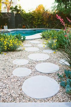 Circles of cement set in a bed of crushed rock look almost like a trail of bubbles leading to this pool. We offer walkway and pool design and installation in the Minneapolis MN area. http://www.aldmn.com