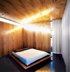 The austere bedroom in Thomas Bercy's Austin, Texas residence is warmed by wood paneling and a curtain running the length of the window wall. Bercy Chen Studio | Photo by Denise Prince Martin.