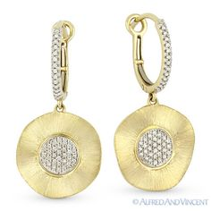 The featured earrings are crafted from 14k yellow gold and showcase matte-finished wavy-circle designs with white gold centerpieces set with round cut diamonds. The wavy circles then dangle from huggie posts also adorned with round cut diamonds and finished with lever-latches for secure wear.