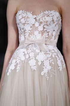 We love the intricate lace detail (and pretty bow!) on this blush pink wedding dress Mira Swillinger