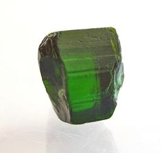 Elbaite, Tourmaline.    Locality: Dudley pegmatite, Penneshaw, Dudley Peninsula, Kangaroo Island, South Australia, Australia A gemmy green Tourmaline section collected in approx 1991 from the weathered Dudley Pegmatite workings. Piece measures 14mm tall x 10mm wide.