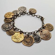 """Vintage metal buttons get SMASHED with a hammer and are transformed into """"antique coins"""". Absolutely perfect for charm bracelets!"""