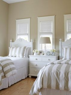 One large headboard was used to make two twin headboards. Creamy latte-color walls match perfectly with striped bedding and give the room a serene quality. A dresser between the beds adds extra storage space to the room.