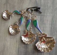 These are our new mermaid spoons which feature beautiful silver metal mermaids with colorful tails. The measuring portion of the mermaid measuring spoon is in a shell shape with the handle being the m