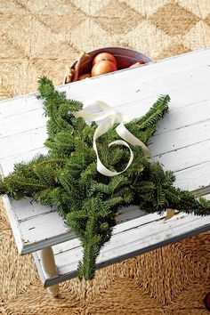 Hang a Star Wreath - Four Crafts for Your Extra Christmas Tree Branches - Southernliving. Cut out a large star shape from cardboard. Gather enough evergreen scraps to completely cover it. Working one point at a time, hot-glue the branches to the cardboard. Attach a ribbon to the back of one point for hanging.