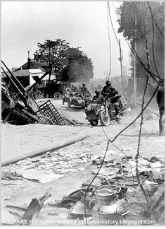 German soldiers move through a devastated French village