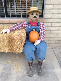 Scarecrow with red plaid shirt, bib overalls, and burlap face, sitting on a bale of straw, outdoors. I Love Fall!