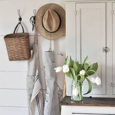 Vintage Farmhouse Decor A simple Spring decorating idea for the farmhouse. Fresh white tulips, an old basket, aprons and a straw hat. Spring Farmhouse Decorating, Home Decor Kitchen, Decor, Spring Decor, Spring Home Decor, Primitive Decorating, Simple Decor, Country Farmhouse Decor, Country House Decor