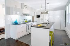Appealing kitchen design with shiny grey marble flooring with glamorous shiny kitchen cabinet and kitchen island with sparkling backsplash and amusing green stools and cool blue glass decor