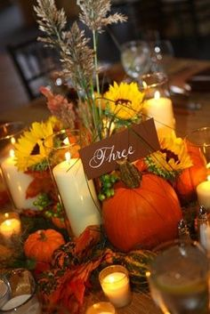This centerpiece filled with fall staples such as pumpkins, squash, sunflowers and stunning candles is perfect for a fall wedding.