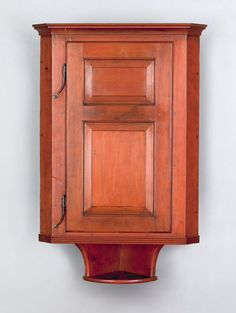"""Pook & Pook. October 24th & 25th 2008. Lot 695.  Estimated: $1000 - $2000. Realized Price: $3744. Pennsylvania poplar hanging corner cupboard, the raised panel door with rattail hinges and a lower shelf, 34"""" h., 21"""" w."""