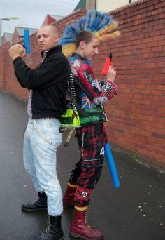 Skin and punk back to back, blue and orange mohawk, toy guns