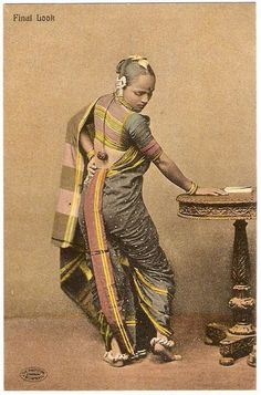 This postcard was printed in subtle colors – a nice change from some of the garish attempts to enliven earlier Indian views.  The model shows off a saree draped in the Marwari style of kaccha.  It is said that this saree gave the women of Maharashtra an elegant gait.  For the best effect, a nine-yard saree was woven with reversible borders to make the famed back view (with that striped edge runing from waist to foot), so beautiful.