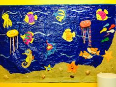 Fondo del mar con serrin, papel celofan azul y peces hechos por los niños decorados con purpurina. Medusas hechas con esponjas y hilos de lana. Peces hechos con globos. Caracolas y petxines de verdad para decorar.