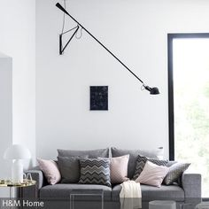 Die auffällige Wandleuchte ist der Hingucker in diesem Wohnzimmer. Die Leuchte ist genau auf das Sofa gerichtet, spendet so ideales Leselicht. Auf dem Sofa mit …