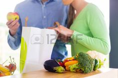 man shopping vegetables: Man and woman unpacking fruits and vegetables out of grocery shopping bag in home kitchen Stock Photo