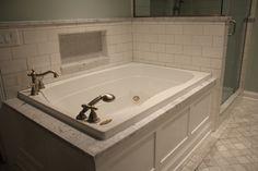 Bathtub with white paneled decorative tub apron