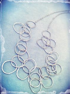 Cascading handcrafted, hammered hoops. The stunning hoops float around the neck bringing to mind champagne bubbles. MEMBER - Papaya Blue