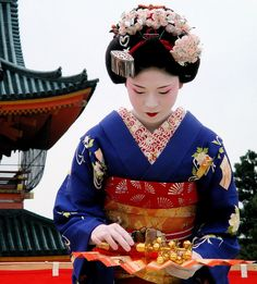 A maiko preforming a traditional dance for a festival.