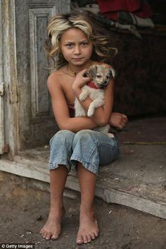 Denise Varga, seven, cuddles her puppy Anka while sitting on the doorstep of the two-room hut she shares with her parents, siblings and gran...