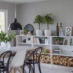 czarna lampa pendant nad drewnianym stołem na kozłach z białymi czarnymi krzesłami, otwarty regał z półkami