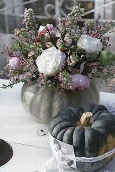 Arrange flowers in gourds, squash, or pumpkins, like this grey one - place  pink and white peonies and whatever else you desire, fresh or dried.