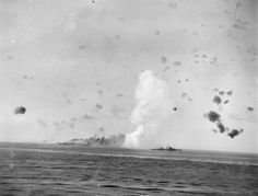 AUG 12 1942 Pitched battles all around Pedestal convoy The bombing of HMS INDOMITABLE: HMS INDOMITABLE on fire after being bombed. A Dido class cruiser, HMS CHARYBDIS, is screening the carrier.