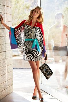 Caftan style cover tunic features an eye catching mixed geometric print. Includes a contrasting waist tie for an adjustable fit. #swimsuits, #swimwear
