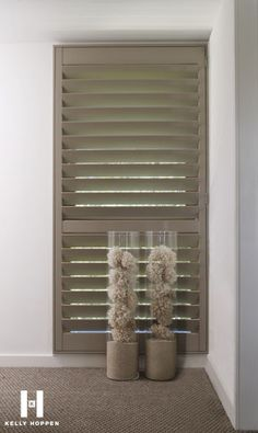 wooden shutters and tall tank vases filled with sponges