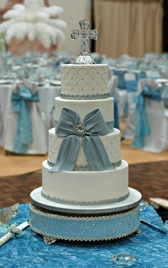 Buttercream Baptism cake.  Silver blue and white, for a Winter themed Baptism.    Complete with a realistic, edible bow. Broach in the center and cross topper are non edible.