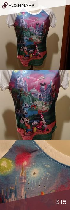 """Disney original tee Women's white tee with short sleeves.  Multiple colorful pictures throughout the front of the top of  Walt Disney World. 100% Polyester. New without tags and has never been worn. 28"""" long down the center back. Back of the tee scoops down longer at the bottom. Nice looking top.  Light weight. Disney Tops Tees - Short Sleeve"""