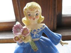 This enchanting ceramic blonde, blue-eyed beauty welcomes Spring and Easter with her bouquet of colorful flowers! Her coloring is so lovely - yellow blonde hair (in classic 1960s flip), big blue eyes, red lips and rosy cheeks, red painted nails - and a lovely blue gown with white trim. I love her pose - one arm extended, bouquet in the other, and one foot forward. She appears to be a bridesmaid walking down the aisle.  Size: Shes 6 3/4 tall and 5 3/4 wide (from fingertips to widest ...